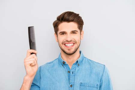 Gelukkige kerel met een stralende glimlach en gezond haar holding comb Stockfoto