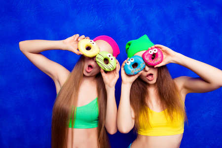 funny glasses: Funny  young girls in hats holding sweet donutes like glasses