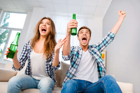 triumphing: Goal! Happy man and woman with beer triumphing with raised hands