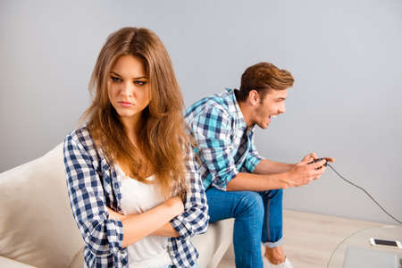 lovers quarrel: Portrait of angry woman with crossed hands while her boyfriend playing video games