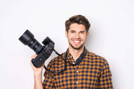 Young cheerful photographer holding camera  while working in studio Stock Photo
