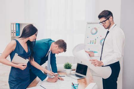 empleados trabajando: Tres colegas que trabajan en nuevo proyecto en la oficina financiera