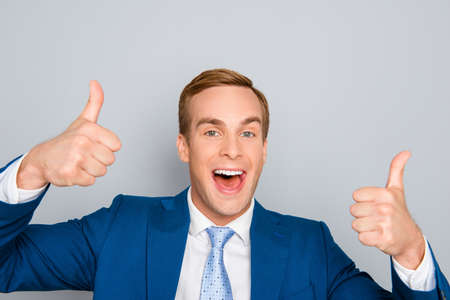Cheerful happy man in blue suit showing thumbs up Stock fotó
