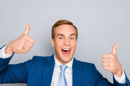 Fröhlich glücklich Mann im blauen Anzug zeigt den Daumen nach oben Standard-Bild
