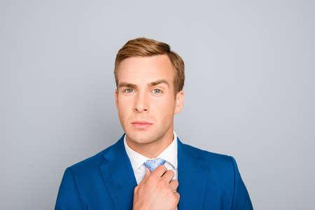 businessman suit: Portrait of handsome businessman in blue suit correcting his tie