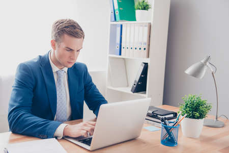concentrated: Concentrated young businessmn in blue suit working with laptop Stock Photo