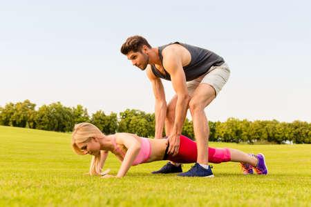pushup: Healthy man helping his girlfriend doing push-up