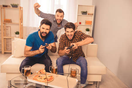 win! excited happy cheerful men play video game with beer and pizza at home