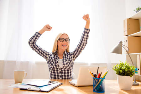 Heureuse femme réussie dans des verres à atteindre le but dans le bureau