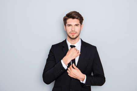 correcting: Portrait of handsome businessman correcting tie on gray background Stock Photo