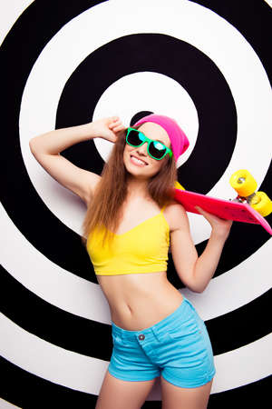 teeny: Happy cheerful woman in glasses holding pink skate board