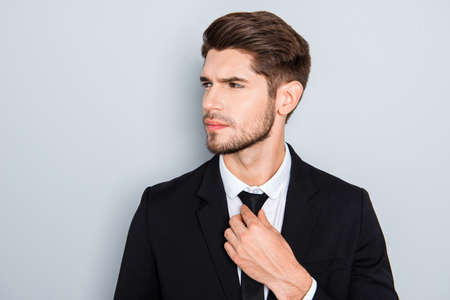 correcting: Portrait of confident young man correcting his tie Stock Photo