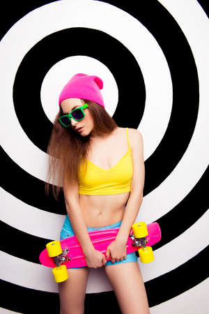 teeny: Portrait of sexy slim woman in hat and glasses with skate Stock Photo