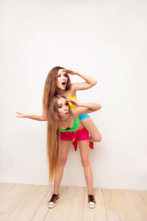 bisexual women: Pretty girl piggybacking her sister and looking way Stock Photo