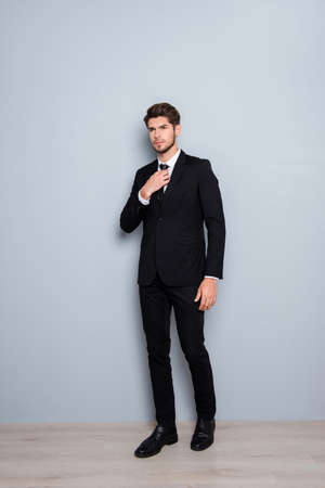 correcting: Full length portrait of young businessman in black suit correcting tie Stock Photo