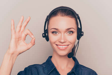 """Cheerful young agent of call center gesturing """"OK"""""""