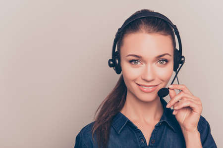 Young smiling agent of call center touching microphone
