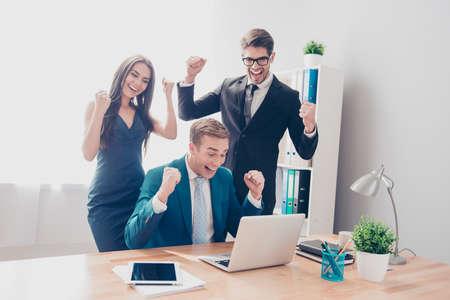 Empresarios de éxito felices triunfando con las manos levantadas y que miran la computadora portátil Foto de archivo - 62052987