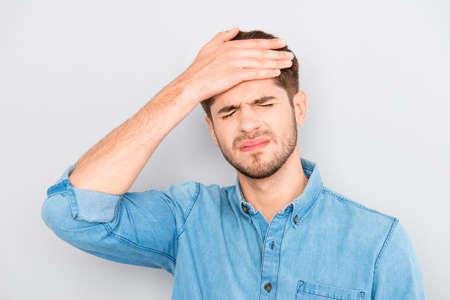 Ritratto di oberati di lavoro uomo triste con mal di testa su sfondo grigio