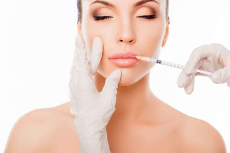Plastic surgery. Young woman geting cosmetic injection in lips