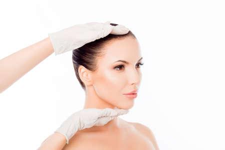 Arts in medische handschoenen die het gezicht van de vrouw na de operatie onderzoekt