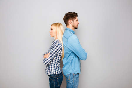Man and woman with crossed hands standing back to back Stock Photo