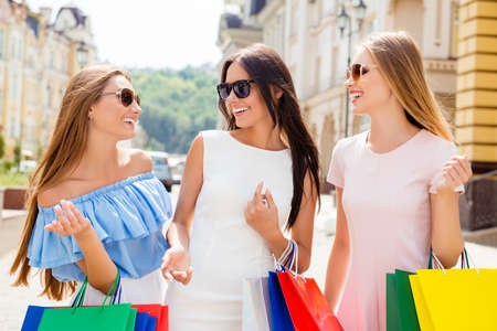 Three happy laughing women with paperbags discussing shopping Stock Photo