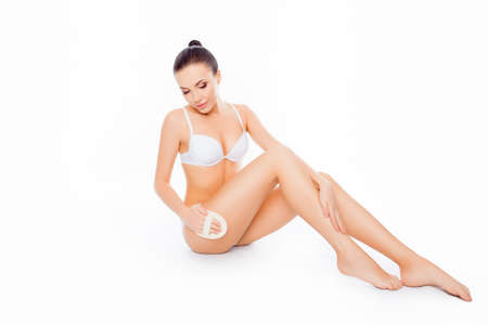 lift hands: Young woman in underwear massaging legs on white background Stock Photo