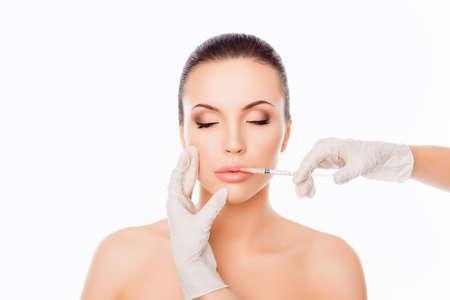 Doctor in de handschoenen geeft vrouw botox-injecties in lippen