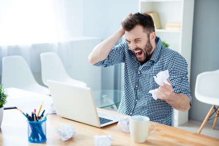 Angry crazy bearded businessman yelling and crumpling paper on his workplace Stock Photo