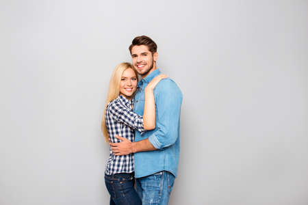 pareja abrazada: Young couple in love embracing isolated on gray background Foto de archivo