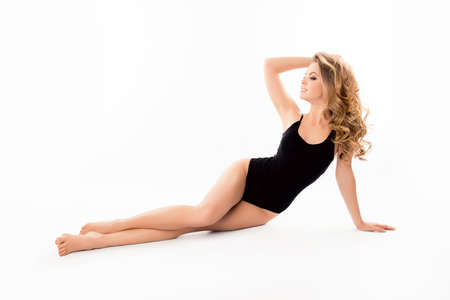 Beautiful slim woman in black swimsuit isolated on white background