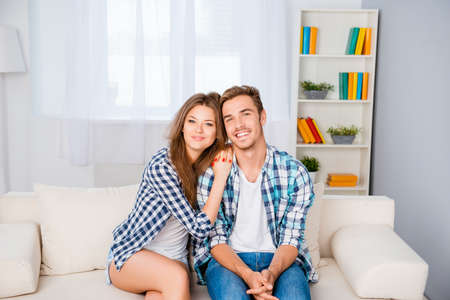 family sofa: happy young smiling family hugging and sitting sofa at home Stock Photo