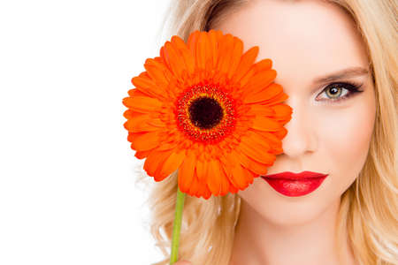 Attractive happy girl hiding half of her face behind gerbera Stock Photo