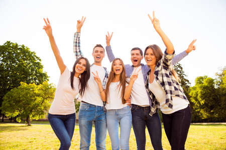 Portrait of happy smiling friends gesturing with raised hands Stock Photo