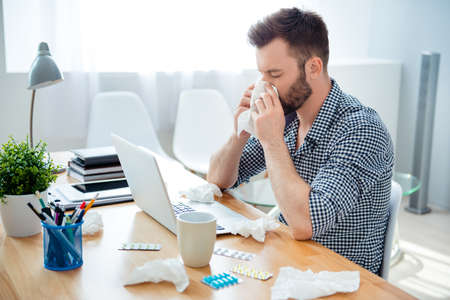 running nose: businessman having cold in the head and sitting at workplace Stock Photo