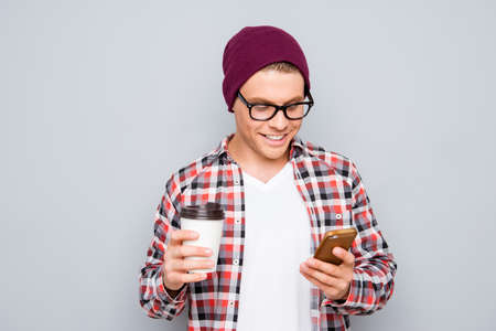 Young hipster in glasses with cup of coffee writing sms on smartphone Stock Photo - 63040261