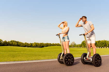 2 way: Happy man and woman riding segway and looking for way