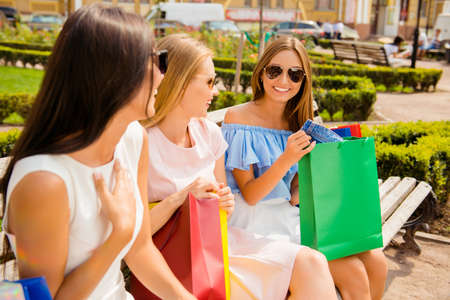 after shopping: Three pretty girls after shopping having gatherings in the park Stock Photo