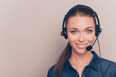caller: Beautiful consultant of call center in headphones on gray background