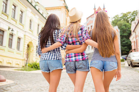 Back view of three shapely women in jeans shorts walking and huging