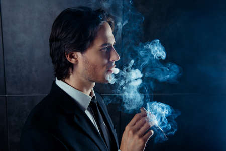smoking a cigar: Side view photo of brutal handsome man  smoking a cigar