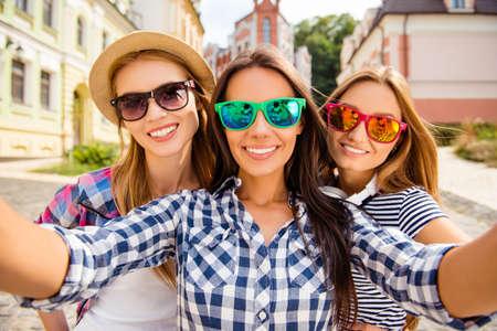 Mujeres bastante felices en vasos haciendo selfie en la ciudad