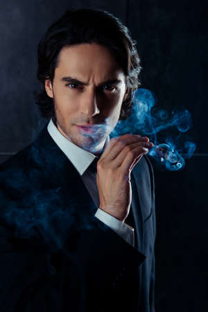 work addicted: Closeup portrait of brutal man  holding a cigar with smoke in hand