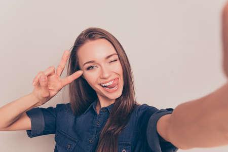 Stripmeisje gebaar v-teken en tonen tong tijdens het maken van selfie Stockfoto