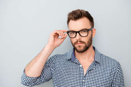 isolated on gray: Serious minded young businessman touching his glasses
