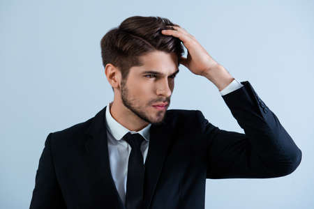 Portrait of handsome young man in black suit combing hair