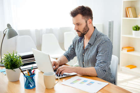 concentrated: Handsome bearded concentrated businessman work on laptop Stock Photo