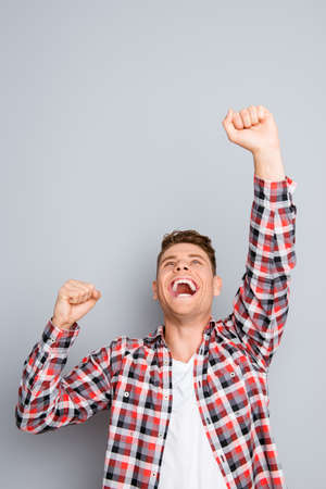 triumphing: Yes! Successful young man triumphing with raised fists