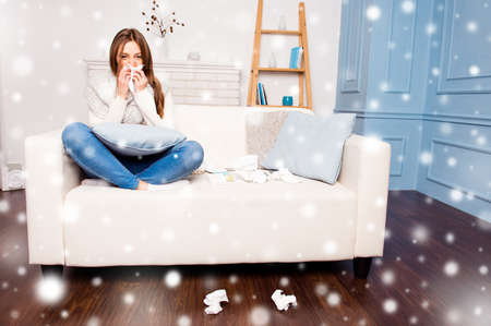 rheum: Sick  girl with fever sneezing in tissue sitting on sofa on xmas